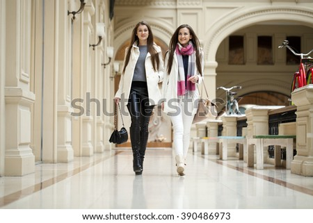 Two young brunette girls walking with shopping at the store - stock photo