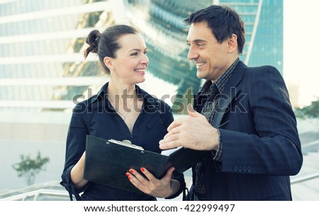 Two young business collegues talking and laughing. Outdoors - stock photo