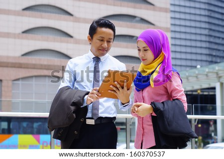 Two young business executive using tablet computer outdoor - stock photo