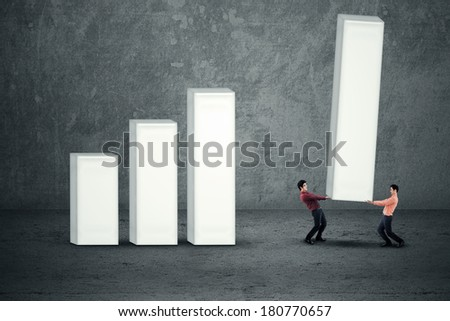 Two young business people building a big graph - stock photo
