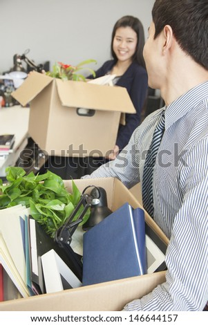 Two young business people carrying boxes with office items - stock photo
