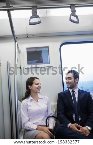 Two young business people sitting and chatting on the subway - stock photo
