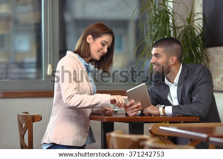 Two young business people using digital tablet on a meeting at coffee shop - stock photo