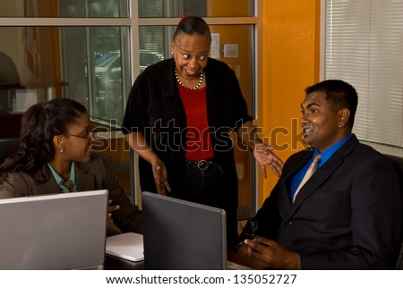 Two young business professionals smile as their more mature, wiser officer manager explains to them how things should be done. - stock photo