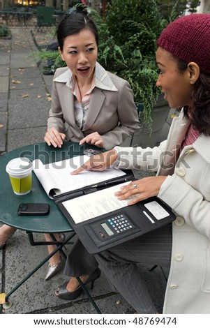 Two young business women discussing a group or team project in the park. - stock photo