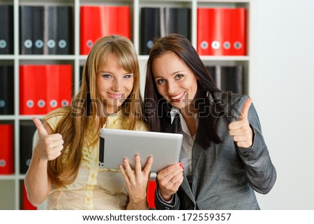 Two young business women with computer tablet in the office. - stock photo