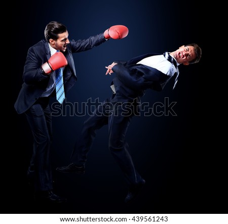 Two young businessman boxing againts dark background - stock photo