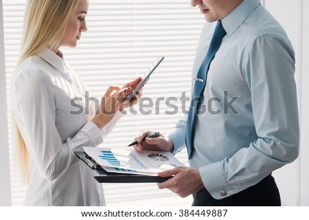 Two young businessman girl and guy looking at graphs standing by the window with blinds - stock photo