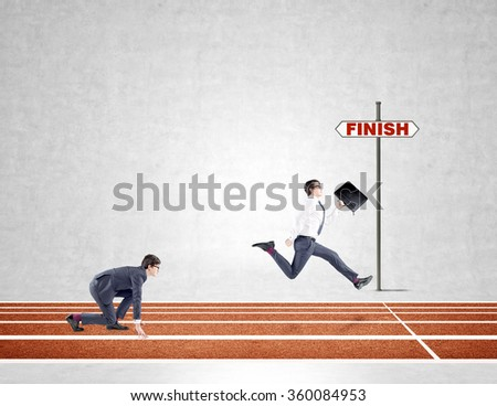 Two young businessmen competing on the track. One in crouch start, the other running forward with a black folder almost crossing the finish line. Concrete background. Concept of competition. - stock photo