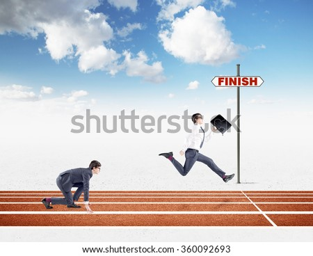 Two young businessmen competing on the track. One in crouch start, the other running forward with a black folder almost crossing the finish line. Blue sky at the background. Concept of competition. - stock photo