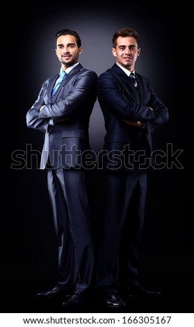 Two young businessmen full body, isolated on black - stock photo