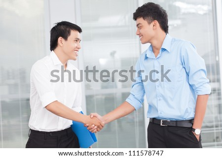 Two young businessmen greeting each other - stock photo