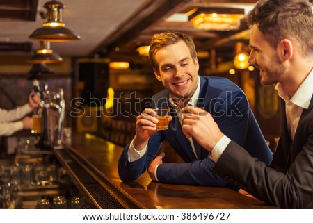 Two young businessmen in suits are smiling and clanging glasses of alcoholic beverage together while sitting at bar counter in pub - stock photo