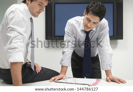 Two young businessmen looking in file folder during a meeting - stock photo