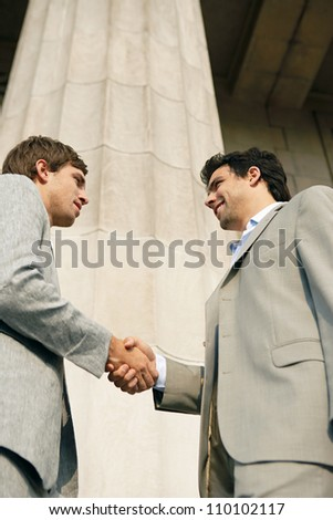Two young businessmen shaking hands in agreement while standing next to a large building's column. - stock photo