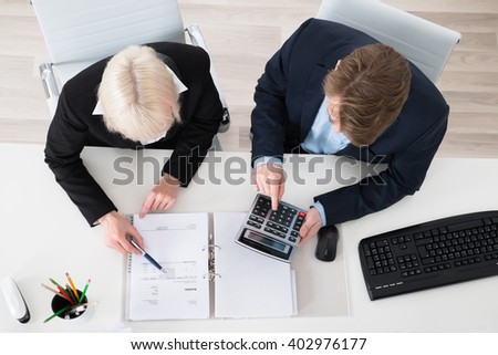 Two Young Businesspeople Calculating Tax In Office - stock photo