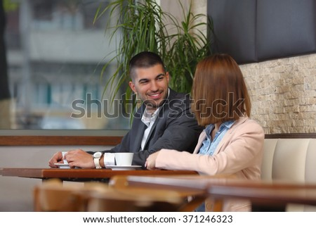 Two young businesspeople on a  meeting in a coffee shop - stock photo