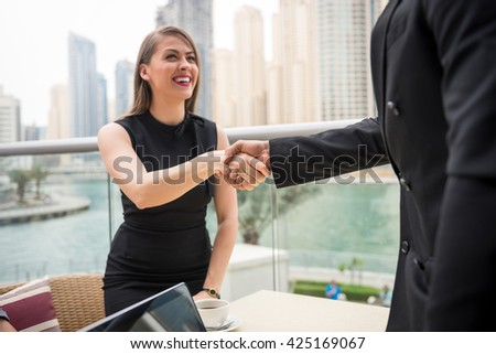 Two young businesswoman handshaking and negotating business. - stock photo