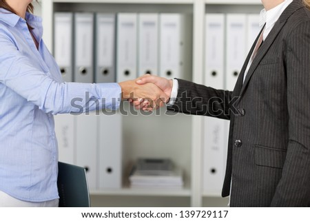 Two young Businesswomans hand shake in office - stock photo