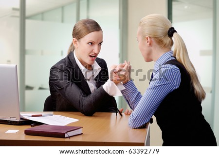 two young businesswomen arm wrestling at the desk in office - stock photo