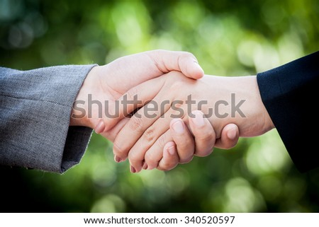 two young businesswomen shaking hands on green bokeh background - stock photo
