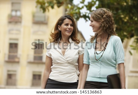 Two young businesswomen walking through town together - stock photo