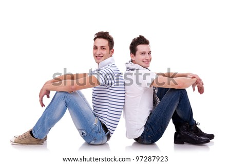 two young casual men sitting back to back on white background and looking at the camera , smiling - stock photo