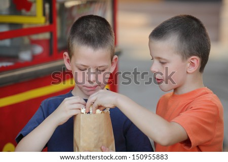 Two young Caucasian boy eating popcorn, real people - stock photo