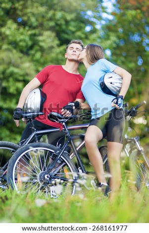 Two Young Caucasian Professional Cyclists Together with Their Bicycles Kissing Outdoors. Vertical Shot - stock photo