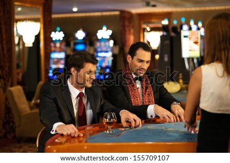 Two young cheerful men behind table in a casino - stock photo