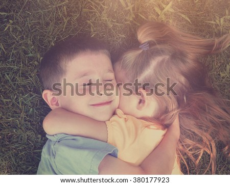 Two young children are hugging on the ground with grass in the background and sunshine for a love or friendship concept. - stock photo