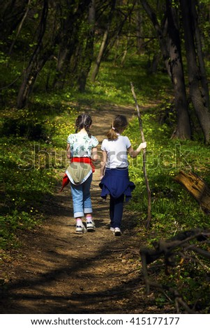 Two young children, girls walking through the woods along a path through the woods - stock photo