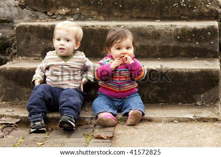 Two Young Children Hanging out on Stair Steps - stock photo