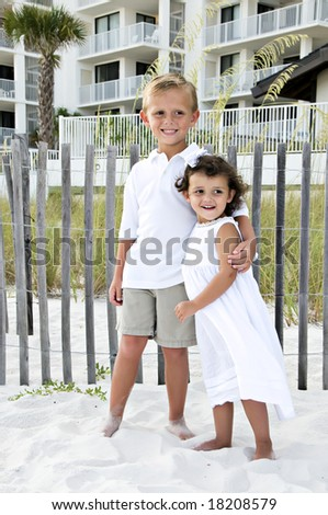 Two young children hugging on the beach - stock photo