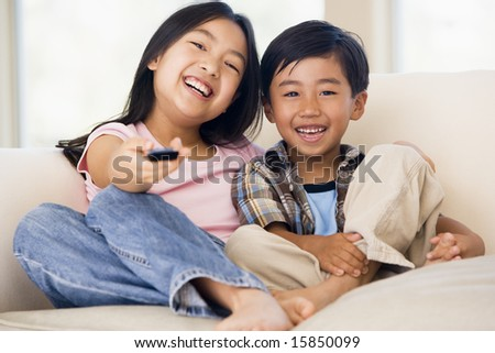 Two young children in living room with remote control smiling - stock photo