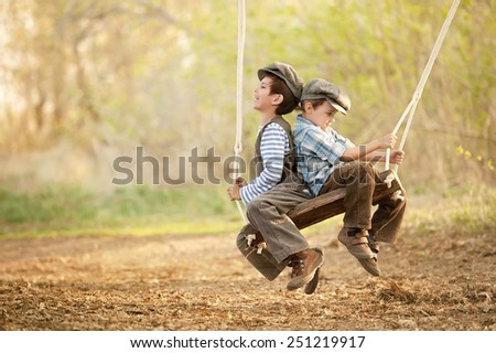 Two young children on a swing sunny summer day - stock photo