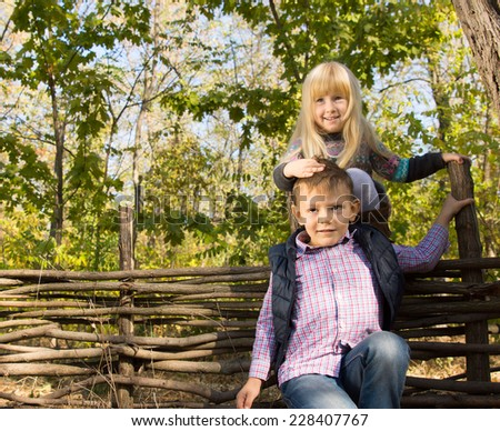 Two young children playing outdoors in woods with the little girl balancing on top of a rustic wooden fence holding onto the boys forehead for balance, both smiling at the camera - stock photo