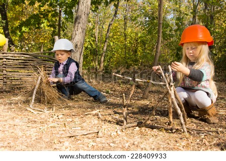 Two young children pretending to be builders or construction workers wearing hardhats and creating frameworks from twigs and branches outdoors in woodland - stock photo