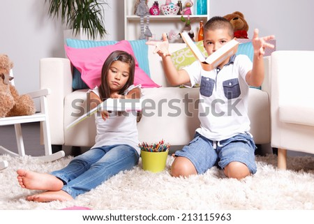 Two young children throwing their books away - stock photo