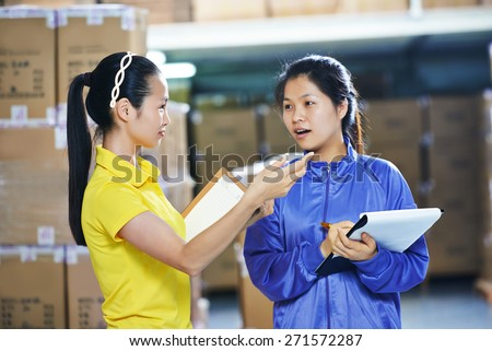 two young chinese female workers in uniform in discussing warehousing system - stock photo