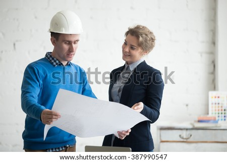 Two young colleagues at meeting looking at project concept, holding blueprints, planning work. Business discussion with construction engineer in hardhat in architectural agency office. Interior shot - stock photo
