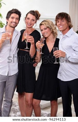 Two young couples drinking champagne - stock photo