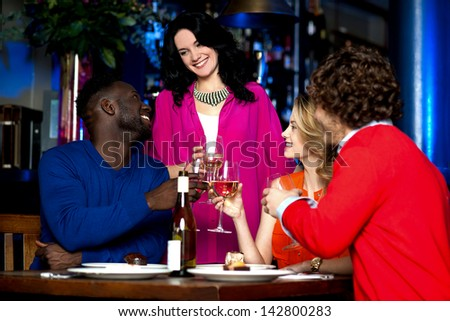Two young couples in club or bar raising a toast. - stock photo