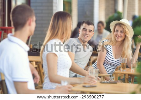 Two young couples sitting in a coffee shop and talking - stock photo