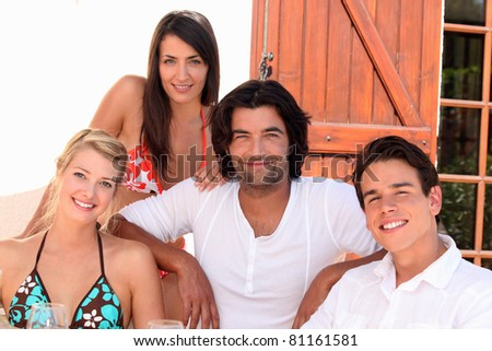 Two young couples sitting in the sunshine - stock photo