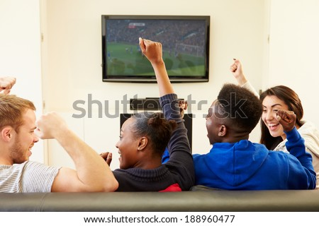 Two Young Couples Watching Television At Home Together - stock photo