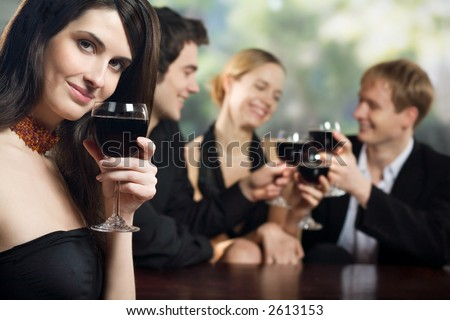 Two young couples with red-wine glasses at celebration or party - stock photo