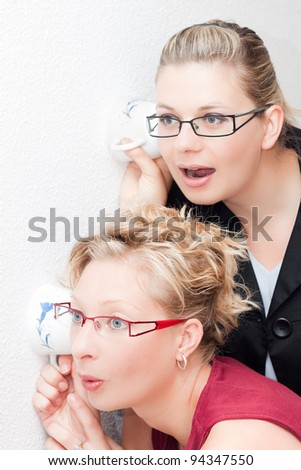Two young Curious women listening through the wall. - stock photo