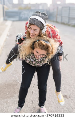 Two young curly and straight blonde hair caucasian woman listening music with headphones, one holding the other on piggyback ride - music, having fun, friendship concept - stock photo