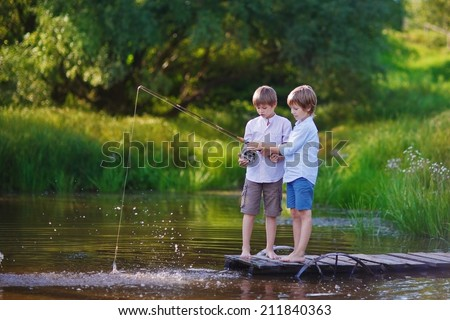 Two young cute boys fishing on a lake in a sunny summer day. Kids are playing. Friendship. - stock photo